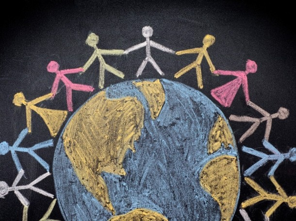 Chalk drawing of a group of people around the world, photo by Professor25/Getty Images