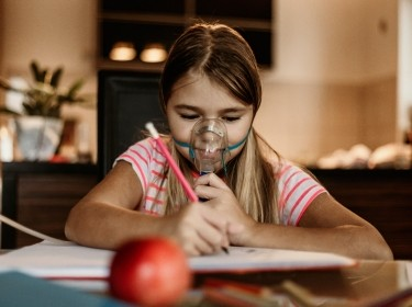 Girl doing homework while using a breathing treatment, photo by anandaBGD/Getty Images