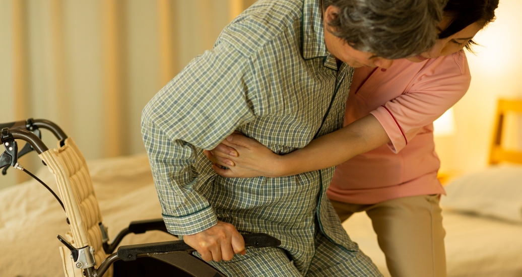Family caregiver helping familymember into bed, photo by byryo/Getty Images
