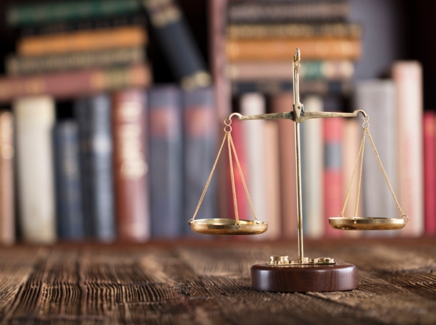 Scales of justice on a table in front of books in a bookcase, photo by Zolnierek/Getty Images