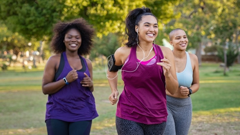Group of women jogging together at park, photo by Ridofranz/Getty Images