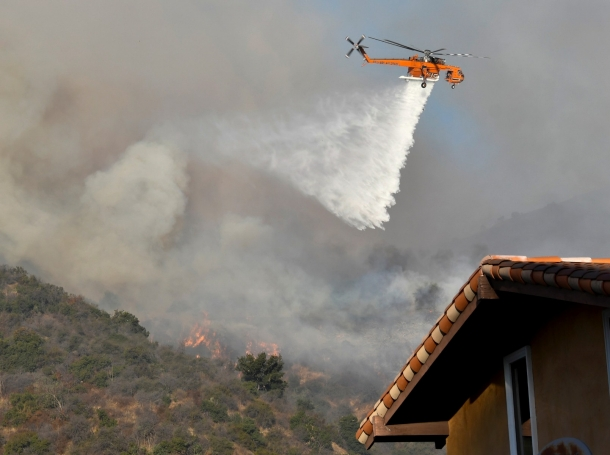 A firefighting helicopter makes a water drop on the Getty Fire as it burns in the hills of West Los Angeles, California, October 28, 2019, photo by Gene Blevins/Reuters