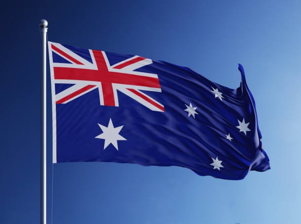 Australian flag waving in blue sky, photo by MicroStockHub/Getty Images