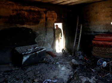 A fighter loyal to Libya's U.N.-backed government looks at a room burned during clashes with troops loyal to Khalifa Haftar in Tripoli, Libya, May 28, 2019, photo by Goran Tomasevic/Reuters