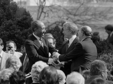 U.S. President Jimmy Carter shakes hands with Egyptian President Anwar Sadat and Israeli Prime Minister Menachem Begin at the signing of the Egyptian-Israeli Peace Treaty on the grounds of the White House, Washington, D.C., March 26, 1979, photo by Warren K. Leffler/Reuters