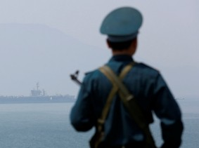A Vietnamese soldier keeps watch in front of U.S. aircraft carrier USS Carl Vinson after its arrival at a port in Danang, Vietnam, March 5, 2018, photo by Nguyen Huy Kham/Reuters