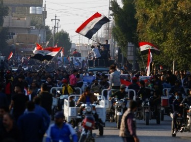 Iraqi demonstrators carry pictures of people who were killed during ongoing anti-government protests in Nassiriya, Iraq, December 4, 2019, photo  by Alaa Al-Marjani/Reuters