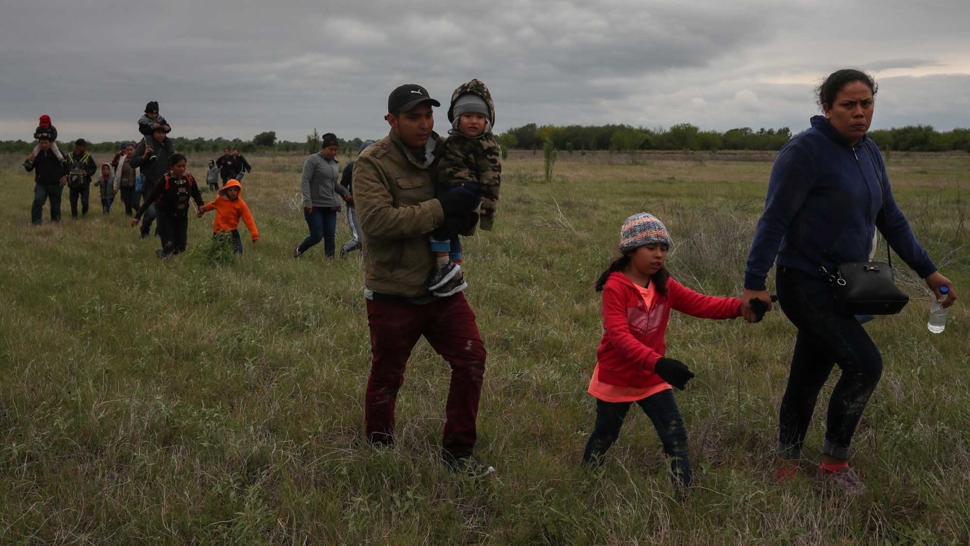 Asylum-seeking families from Central America trek through a field after crossing the Rio Grande River, Penitas, Texas, March 31, 2019, photo by Adrees Latif/Reuters