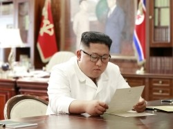 North Korean leader Kim Jong Un reads a letter from U.S. President Donald Trump in Pyongyang, photo by North Korea's Korean Central News Agency via Reuters