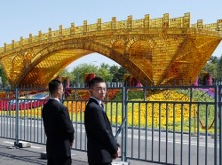 "Security personnel stand guard near a ""Golden Bridge on Silk Road"" decoration for the Belt and Road Forum outside the China National Convention Center in Beijing, China, April 25, 2019, photo by Jason Lee/Reuters"