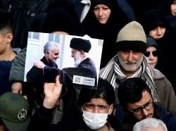 A demonstrator holds a picture of Iranian Major-General Qassem Soleimani with Supreme Leader Ayatollah Ali Khamenei during a protest in Tehran, Iran, January 3, 2020, photo by Nazanin Tabatabaee/West Asia News Agency/Reuters