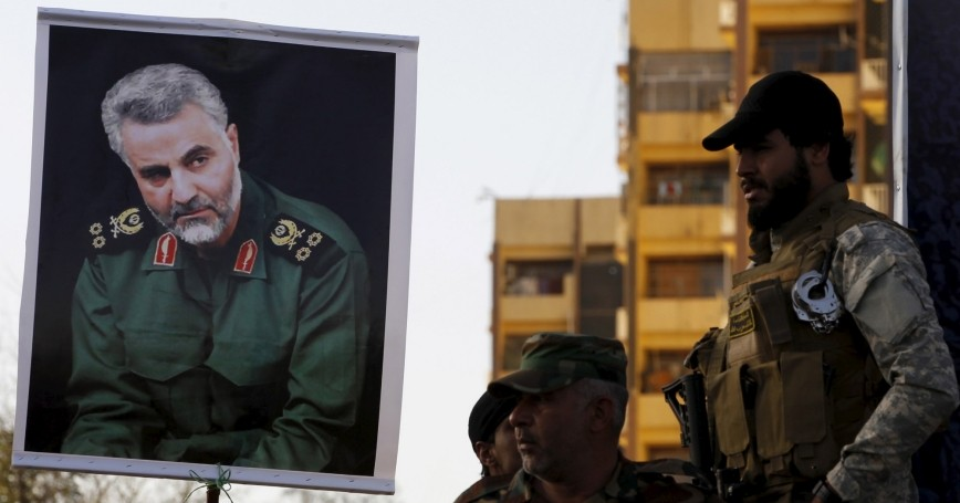 Militia members hold a portrait of Iranian Commander Major General Qassem Soleimani during a protest of an air campaign in Yemen by a Saudi-led coalition, Baghdad, March 31, 2015, photo by Thaier Al-Sudani/Reuters