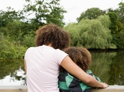 Woman with arm around a child, looking at a lake, photo by Image Source/Getty Images