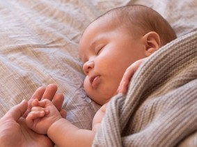 Sleeping baby with adult hand holding baby's hand, photo by Amax Photo/Getty Images