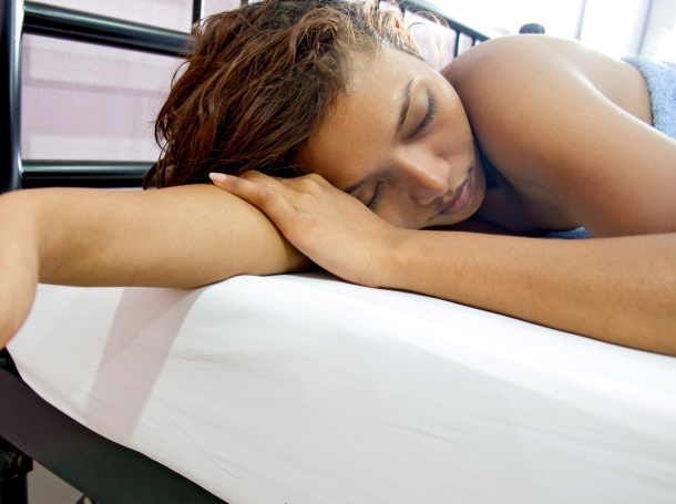 Young woman sleeping in a bed, photo by riskms/Getty Images