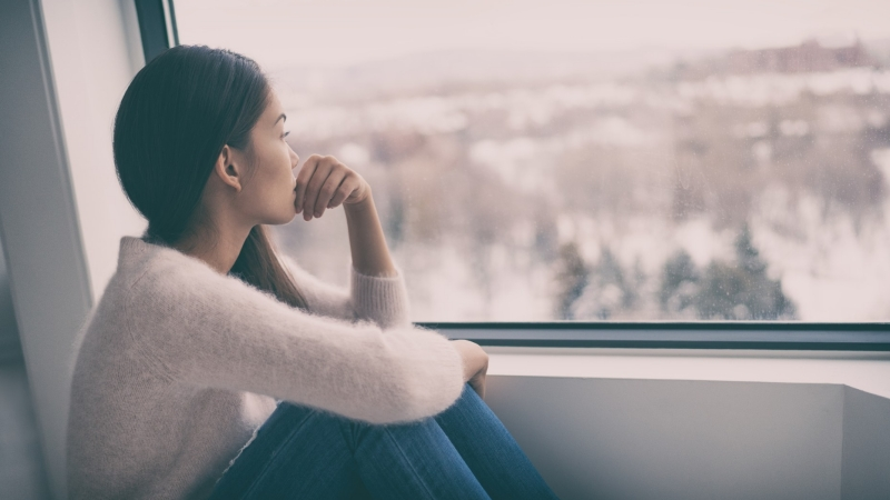 A young woman looks out the window during winter, photo by Maridav/Adobe Stock
