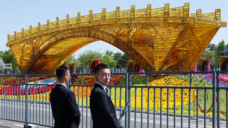 """Security personnel stand guard near a """"Golden Bridge on Silk Road"""" decoration for the Belt and Road Forum outside the China National Convention Center in Beijing, China, April 25, 2019, photo by Jason Lee/Reuters"""