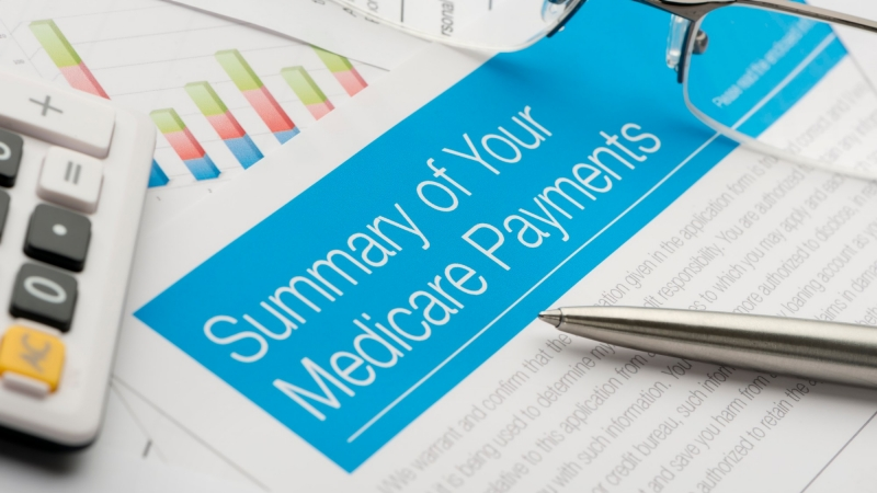 Summary of Medicare benefits with pen, glasses, and calculator, photo by courtneyk/Getty Images