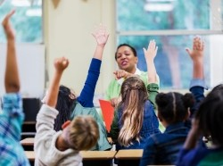 Elementary students raising their hands in class, photo by kali9/Getty Images