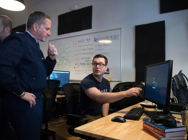Senior Airman Ken McDougall shows Air Force Chief of Staff Gen. David L. Goldfein the results of code Goldfein wrote during a visit to Project Kessel Run in Boston, Massachusetts, December 6, 2018, photo by Jerry Saslav/U.S. Air Force