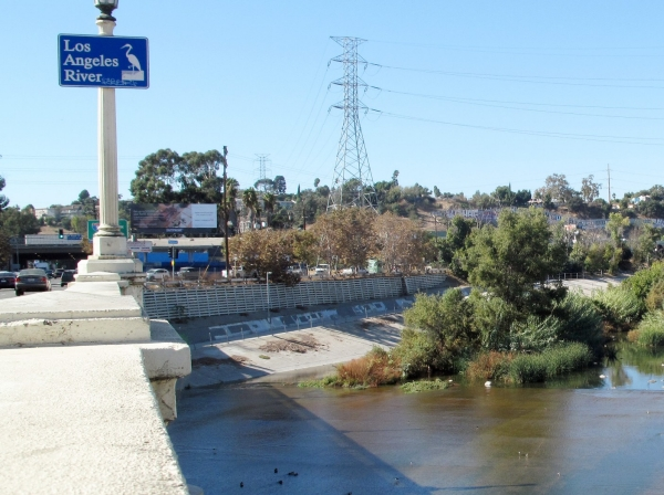 "Looking west along the Los Angeles River from the Fletcher Drive Bridge, <a href=""https://upload.wikimedia.org/wikipedia/commons/c/c1/Los_Angeles_River_from_Fletcher_Drive_Bridge_2019.jpg"">photo</a> by Downtowngal / <a href=""https://creativecommons.org/licenses/by-sa/4.0/deed.en"">CC BY-SA 4.0</a>"