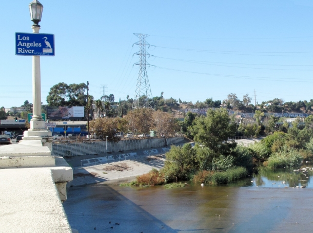"""Looking west along the Los Angeles River from the Fletcher Drive Bridge, <a href=""""https://upload.wikimedia.org/wikipedia/commons/c/c1/Los_Angeles_River_from_Fletcher_Drive_Bridge_2019.jpg"""">photo</a> by Downtowngal / <a href=""""https://creativecommons.org/licenses/by-sa/4.0/deed.en"""">CC BY-SA 4.0</a>"""