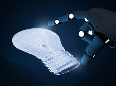 Robot hand touching CGI lightbulb, photo by PhonlamaiPhoto/Getty Images