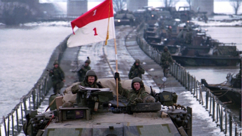 Americans, providing the main muscle for a global peace force, cross a pontoon bridge toward the northern Bosnian town of Orasje, December 31, 1995, photo by Petar Kudjundzic/Reuters