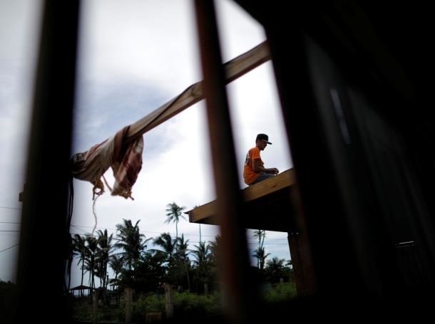 A local resident works repairing a house roof a year after Hurricane Maria devastated Puerto Rico, near Barceloneta, Puerto Rico, September 18, 2018, photo by Carlos Barria/Reuters