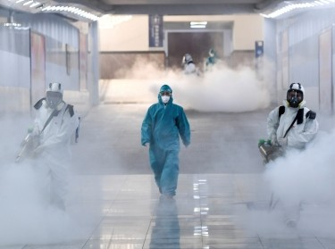 Volunteers in protective suits disinfect a railway station as China tries to contain an outbreak of coronavirus, Changsha, Hunan province, February 4, 2020, photo by Stringer/Reuters