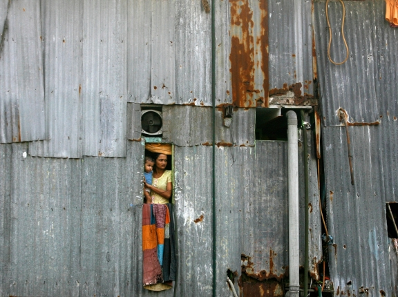 A woman holding a baby looks out of a window from a shanty in Dharavi, Mumbai, India, October 15, 2009, photo by Arko Datta/Reuters