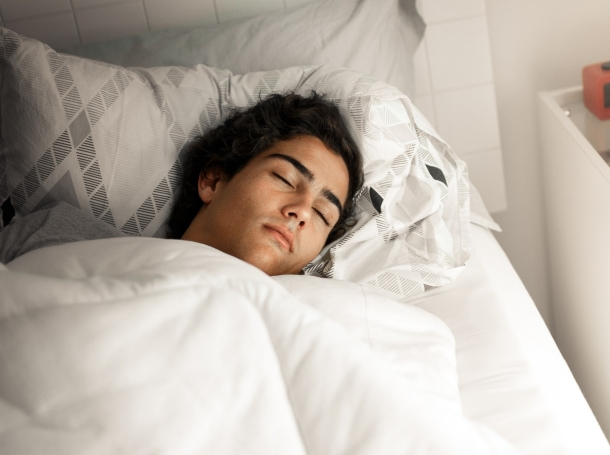 Teen boy sleeping in bed, photo by Capuski/Getty Images