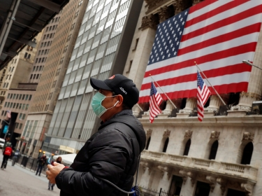 A man wears a mask while walking past the New York Stock Exchange in New York City, March 17, 2020, photo by Lucas Jackson/Reuters