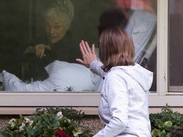 A woman visits her mother who has tested positive for coronavirus at a Seattle-area nursing home, the epicenter of one of the biggest outbreaks in the United States, in Kirkland, Washington, March 11, 2020, photo by Jason Redmond/Reuters