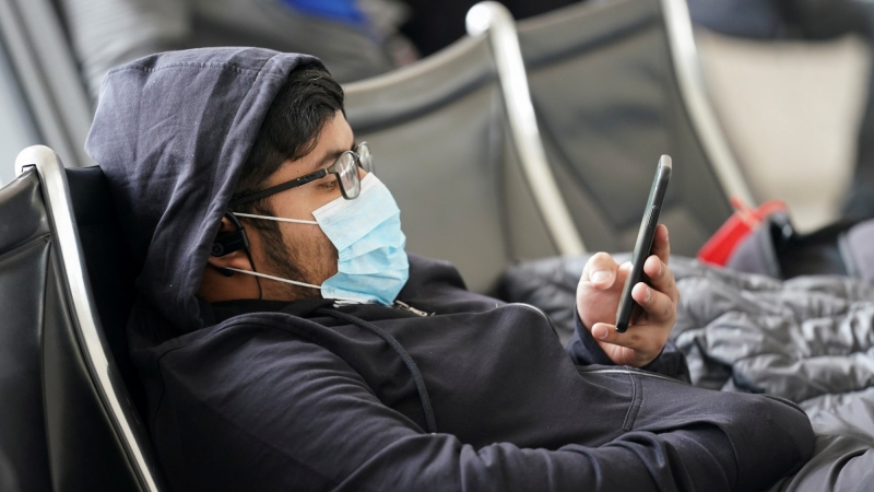 A man wearing a face mask looks at his phone at Dulles International Airport in Dulles, Virginia, March 12, 2020, photo by Kevin Lamarque/Reuters