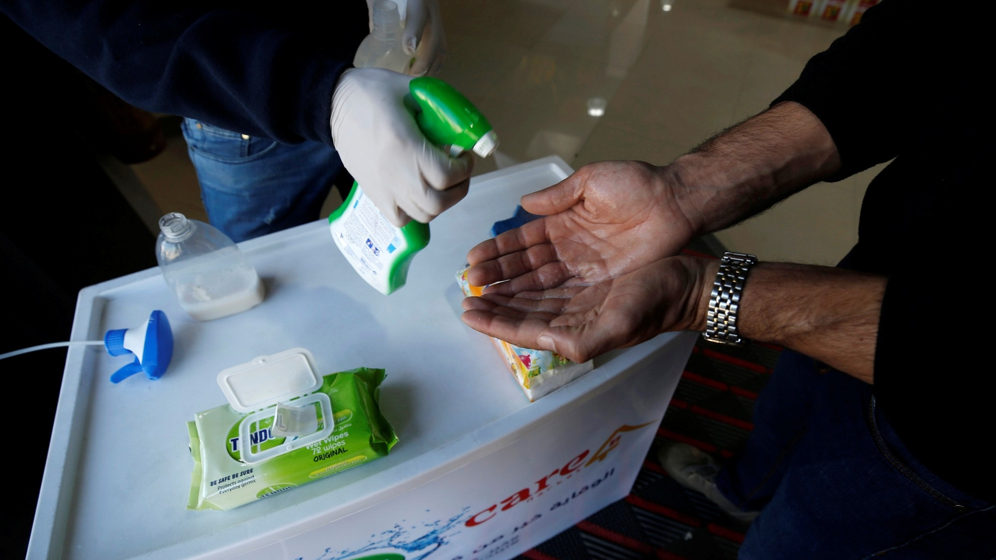 A Palestinian worker sanitizes the hands of a customer at a supermarket in Gaza City, March 8, 2020, photo by Mohammed Salem/Reuters