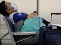 A traveler takes a nap following reports of the coronavirus, Galeao International Airport, Rio de Janeiro, Brazil, March 6, 2020, photo by Ricardo Moraes/Reuters