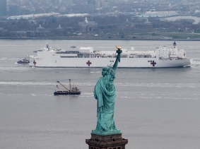 The U.S. Navy hospital ship Comfort passes the Statue of Liberty as it enters New York Harbor during the COVID-19 outbreak, March 30, 2020, photo by Mike Segar/Reuters