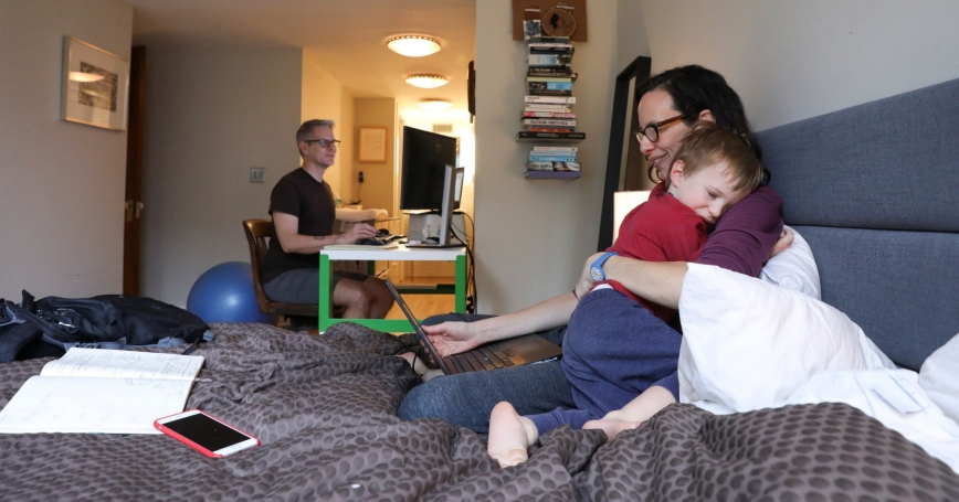 Naomi Hassebroek holds her son Felix while working with her husband Doug Hassebroek at their home, during the COVID-19 pandemic in Brooklyn, New York, March 19, 2020, photo by Caitlin Ochs/Reuters