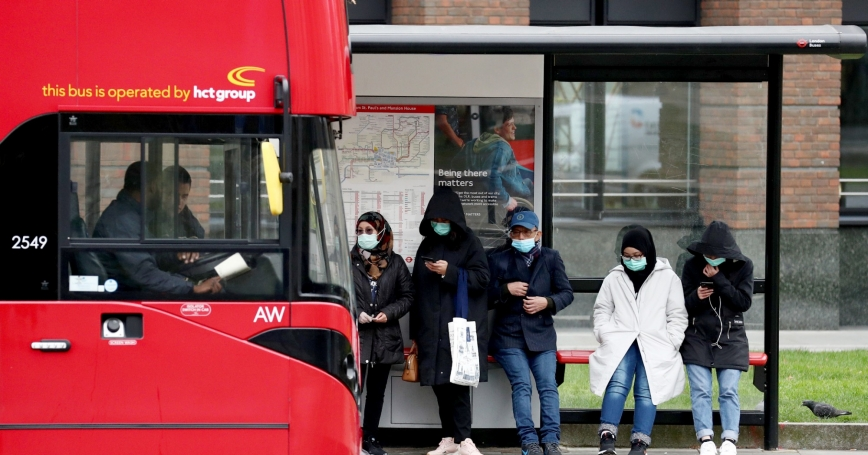 People wearing protective face masks wait for a bus in front of St. Paul's Cathedral in London, Britain, March 19, 2020, photo by Simon Dawson/Reuters