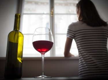 Woman looking out window with wine bottle and glass on table in foreground, photo by kieferpix/Getty Images