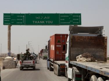 Trucks wait to cross the Afghanistan-Iran border in Zaranj, Afghanistan, May 10, 2011, photo by Sgt. Mallory VanderSchans/U.S. Marine Corps