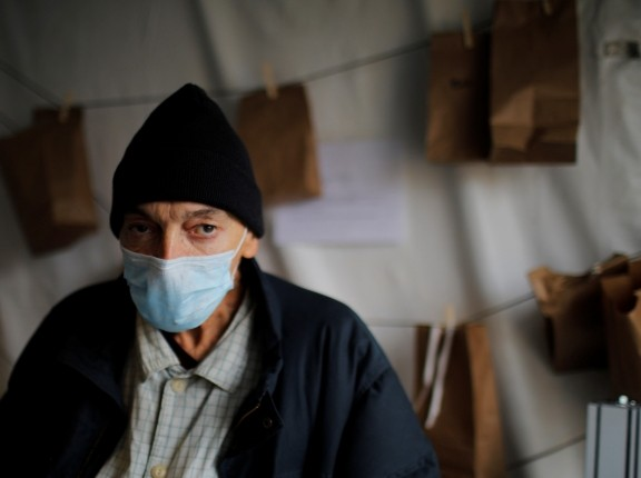 Kevin Keeley, who has been experiencing homelessness for eight months and may have come into contact with someone with COVID-19, stands outside a quarantine tent in Boston, Massachusetts, April 2, 2020, photo by Brian Snyder/Reuters