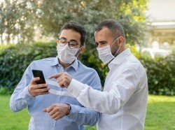 Two men looking at a phone and wearing face masks, photo by ozgurdonmaz/Getty Images