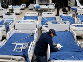 A worker checks part of a delivery of hospital beds to The Mount Sinai Hospital during the COVID-19 outbreak, New York City, March 31, 2020, photo by Andrew Kelly/Reuters