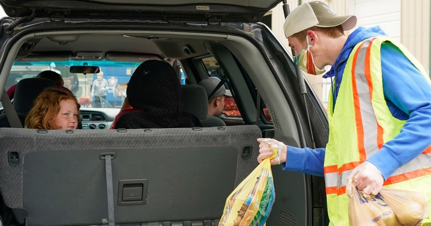 A volunteer with Highpoint Charitable Services loads groceries into the car of a family in need at a food bank in LaGrange, Kentucky, April 13, 2020, photo by Bryan Woolston/Reuters