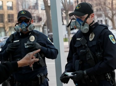 Police officers from the Madison Police Department wearing face protective gear take information from a man at a bus stop in Madison, Wisconsin, April 17, 2020, photo by Shannon Stapleton/Reuters