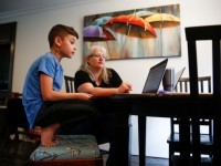 Chrissy Brackett and grandson Caidence Miller learn to navigate an online learning system at her home in Woodinville, Washington, March 11, 2020