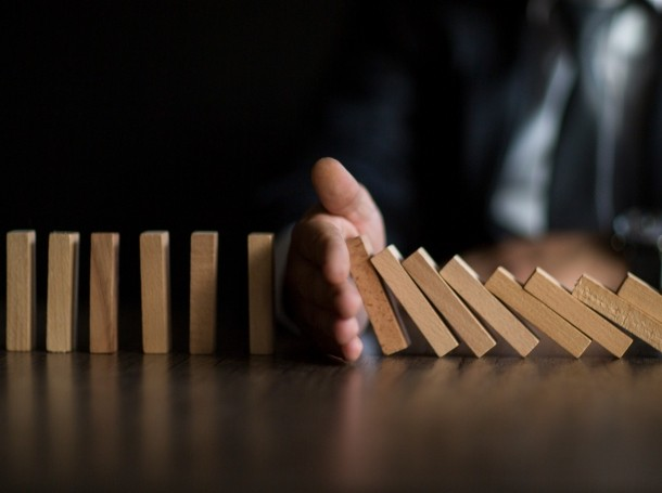 Businessman stops domino effect, photo by ridvan_celik/Getty Images