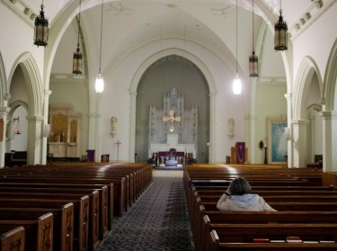 A woman prays alone in Blessed Sacrament Catholic Church on Palm Sunday amid the COVID-19 outbreak in Worcester, Massachusetts, April 5, 2020, photo by Brian Snyder/Reuters